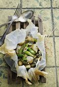 Potatoes, green asparagus and blue cheese in parchment paper