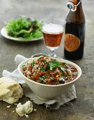 Beef ragout with bread and salad served with a beer