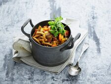 Vegetable stew with beef, mushrooms and pasta in a small pot