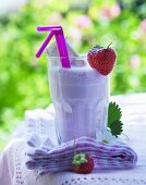 A strawberry milkshake on a table outside