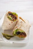A burrito filled with beans, beef, guacamole, lettuce and tomato rice