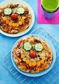 Zwei kleine Pizzen mit Gemüsegesichtern für Kinder