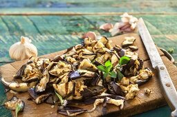 Chopped grilled aubergine and peppermint on a rustic wooden board