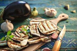 Grilled aubergine slices, garlic and peppermint on a rustic wooden table