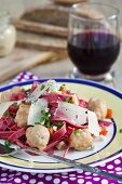Homemade beetroot pasta with meatballs and cheese