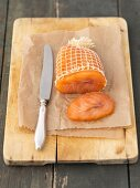 Smoked salmon in a net on a chopping board