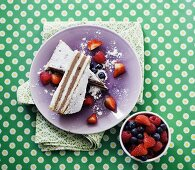Two slices of chocolate cream tart on a purple plate served with fresh berries