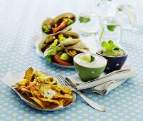 Various Tex-Mex dishes: nachos with cheese, sour cream, guacamole, tortilla wraps with a vegetable filling