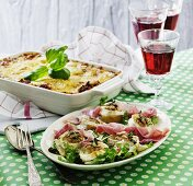 Baked goat's cheese with walnuts on a Parma ham salad with a lasagne in the background