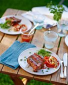 Grilled pork ribs with a pepper salad and ketchup