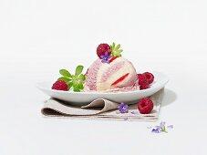 A raspberry ice cream bomb with raspberries, woodruff and flowers