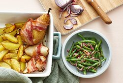 Bacon-wrapped pears with roast potatoes and a bean and onion salad