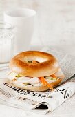 A bagel with turkey breast and carrots on a newspaper