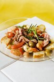 Bread salad with mortadella, white beans, tomatoes and olive