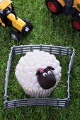 An Easter lamb cupcake and toy tractors on a grass surface