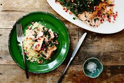 Oven-baked salmon with a herb crust, couscous and pomegranate seeds