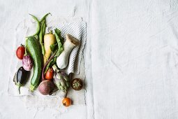 Various types of vegetables and king trumpet mushrooms on a linen cloth