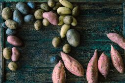 Various types of potatoes and sweet potatoes on a wooden surface
