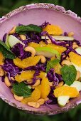 Red cabbage salad with oranges, apples and cashew nuts