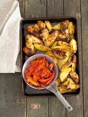 Grilled chicken wings with potato wedges and peppers