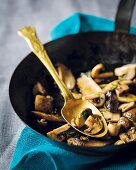 Mixed mushrooms in a frying pan with a spoon