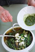 Soup being garnished with pesto