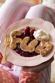 Letter-shaped pancake on berry purée with cream
