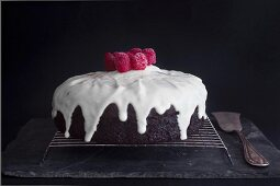 A Red Velvet cake with icing sugar and raspberries on a wire rack
