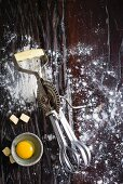 An old hand mixer, flour, a cracked open egg and diced butter
