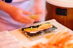 Sushi with salmon and nori being made