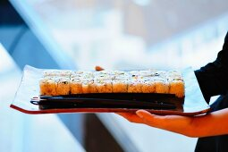 A woman holding a tray of maki sushi