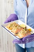 A woman holding a baking tin of baked salmon with a horseradish crust