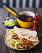 Wraps filled with chickpeas, sloppy Joe sauce and iceberg lettuce