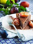 A slice of chocolate cake with roasted plums