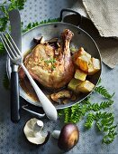 A chicken leg with potatoes and mushrooms