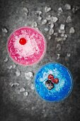 Bright blue and pink frozen cocktails topped with berries and maraschino cherries