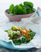 Baked cod with leek, basil, parsley, peppers and lemon in parchment paper