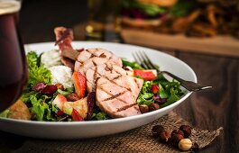 A mixed salad with grilled gammon, pears, strawberries, goat's cheese, crispy ham, hazelnuts and maple vinaigrette