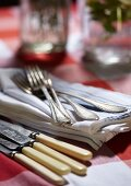 Besteck und Stoffservietten auf rustikalem Tisch