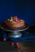 Dark chocolate cake on a metal cake stand with fresh raspberries and mint