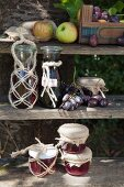 Bottles and jam jars in macrame covers on weathered wooden shelves in autumn