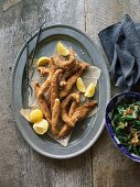 Deep-fried fish with lemon wedges and green cabbage