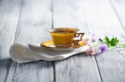 A yellow coffee cup on a napkin with flowers