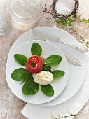 An oven-roasted tomato wrapped in ham with mozzarella on spinach leaves