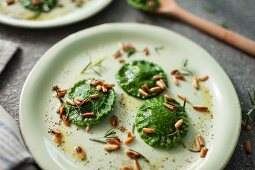Homemade spinach ravioli with roasted pine nuts