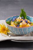 Orange and apple salad with hazelnuts and edible flowers