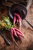 Fresh organic radishes on a wooden table with a sieve