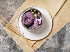 Lavender pasta in a bowl decorated with orchid flowers (seen from above)