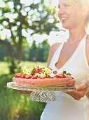 A woman serving a strawberry tart at a garden party