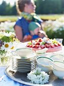 Strawberry tart and teacups on a garden table